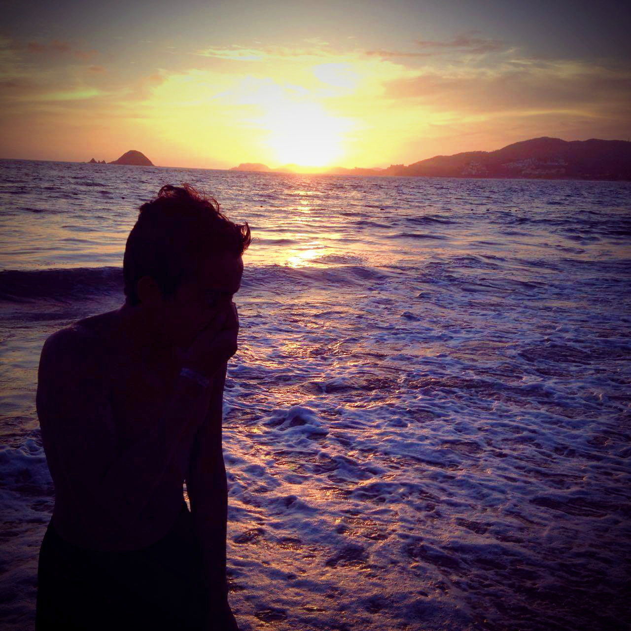 sunset, sea, beauty in nature, water, nature, wave, scenics, orange color, beach, silhouette, one person, standing, real people, sky, tranquil scene, outdoors, tranquility, horizon over water, leisure activity, vacations, lifestyles, women, day, people