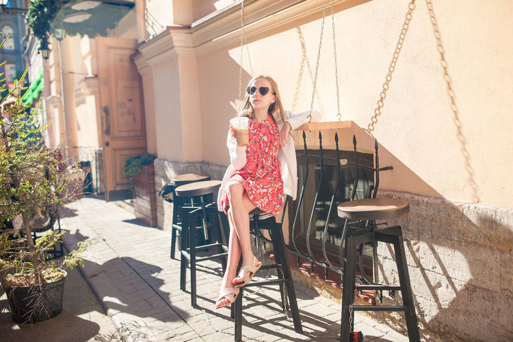 Girl sitting on stool at restaurant