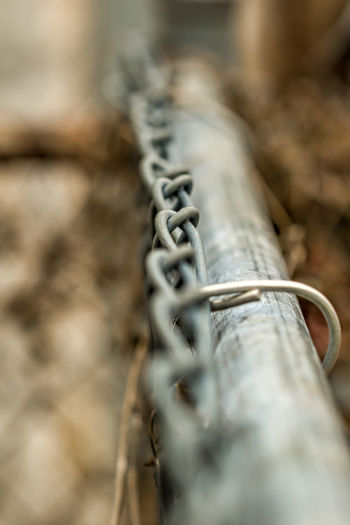 A fence shown in a shallow depth of field and soft background bokeh Climb Pennsylvania Chain Close-up Communication Connection Day Detail Dirt Equipment Fence Focus On Foreground Howard Roberts Indoors  Metal No People Old Segregation  Selective Focus Seperation Silver Colored Single Object Still Life Tied Up Wood - Material