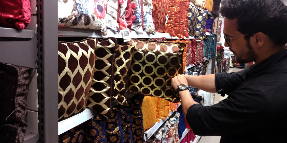 Side view of man looking at pillows in store
