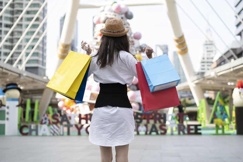 Rear view of woman holding shopping bags while standing on street in city