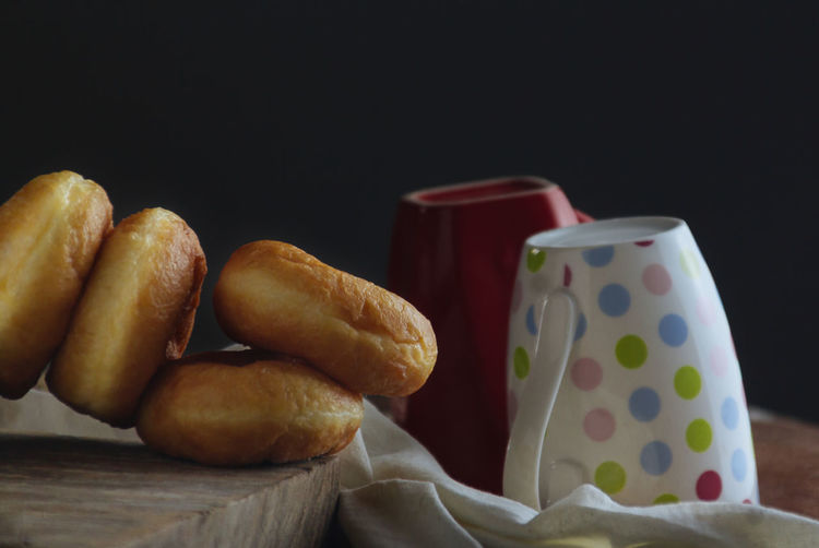 Pastry Donut Food Indoors  Domestic Life Copy Space Food And Drink Still Life Indoors  Freshness Close-up No People Black Background Table Studio Shot Baked Bread Healthy Eating Cup Ready-to-eat Container Focus On Foreground Mug Wellbeing Snack Breakfast Deep Fried  Baked Pastry Item