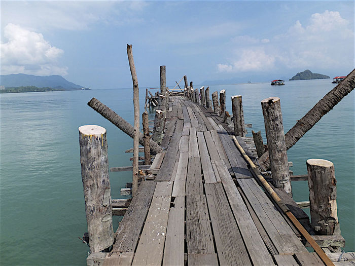 Old Wooden Jetty Over Sea Against Sky