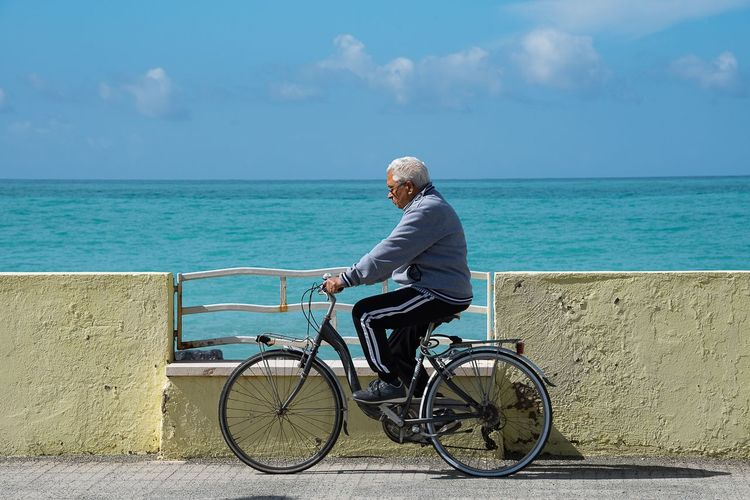Single biker man Bicycle Sea Cycling Full Length Water Horizon Over Water Transportation One Man Only Adult Beach Outdoors