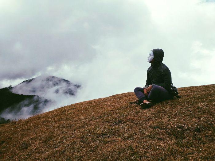 Woman Wearing Mask Sitting On Mountain