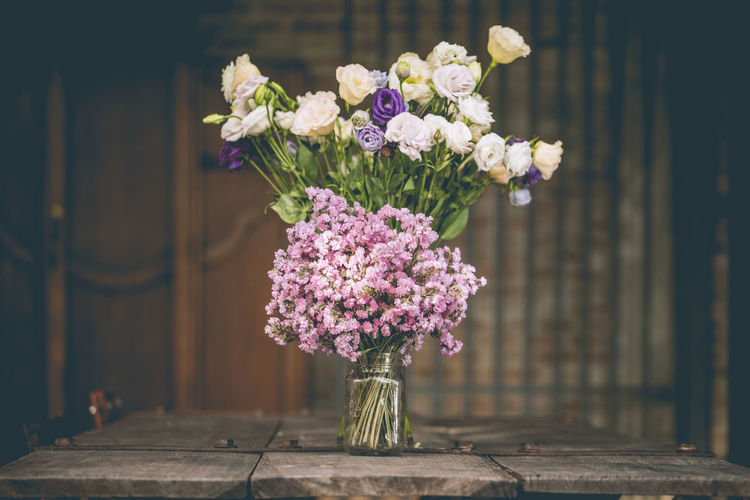 A bouquet of purple flowers in a glass vase on a wooden floor boards of old vintage. the home decor
