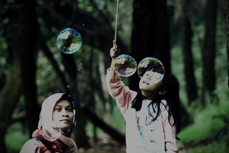 Mother and daughter looking at bubbles in forest