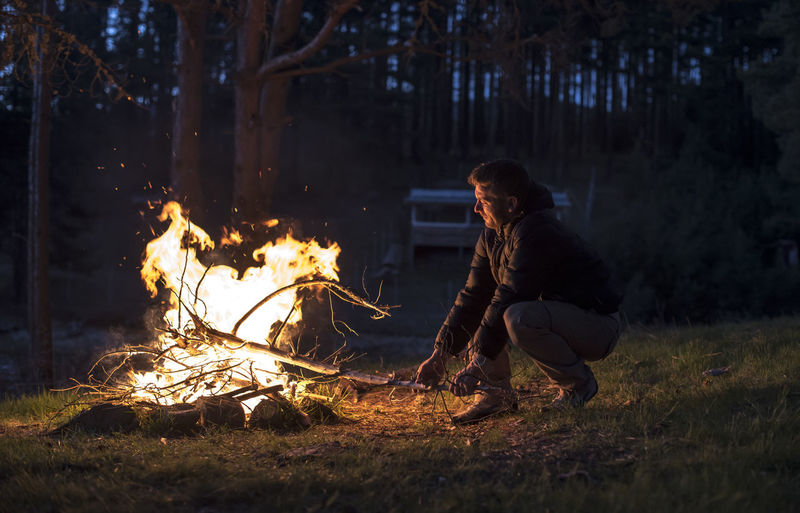 Man with campfire in forest during dusk