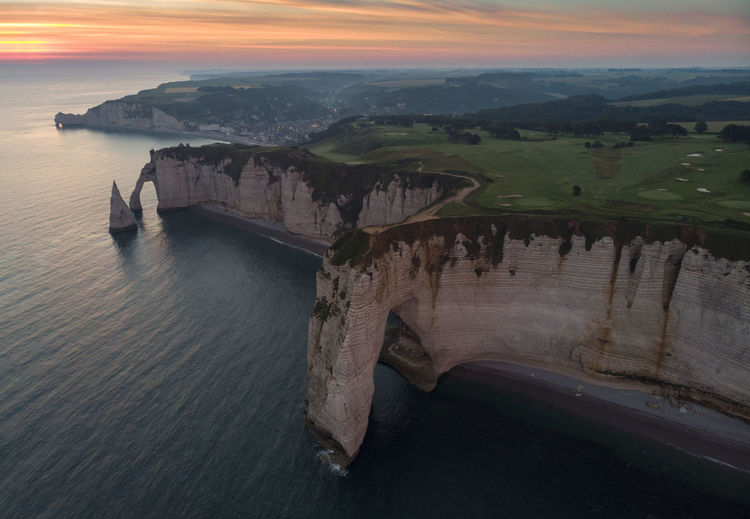 Aerial view of sea by rock formation against sky during sunset