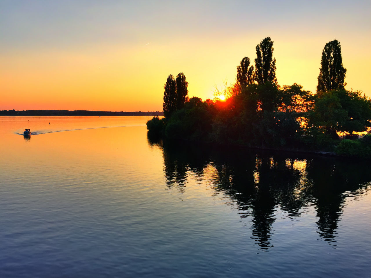 sunset, reflection, beauty in nature, water, silhouette, nature, scenics, sky, tranquility, orange color, tranquil scene, lake, outdoors, waterfront, no people, tree, day