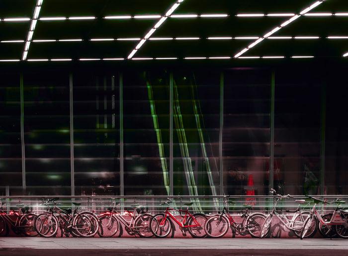 Bicycles on railing against illuminated fence at night