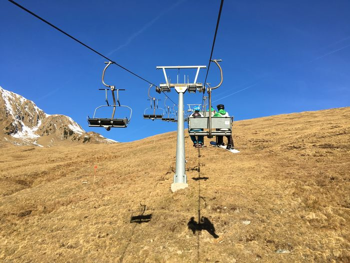 Low Angle View Of People On Ski Lift On Mountain