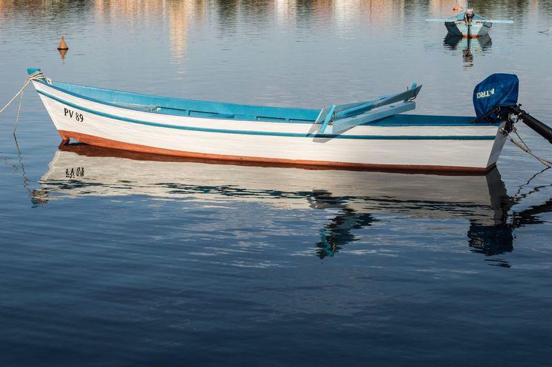 Fishing boat moored in lake against sky