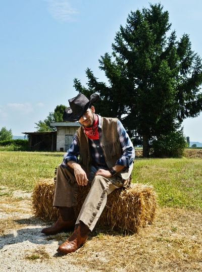 Full length of cowboy sitting on hay at field against sky