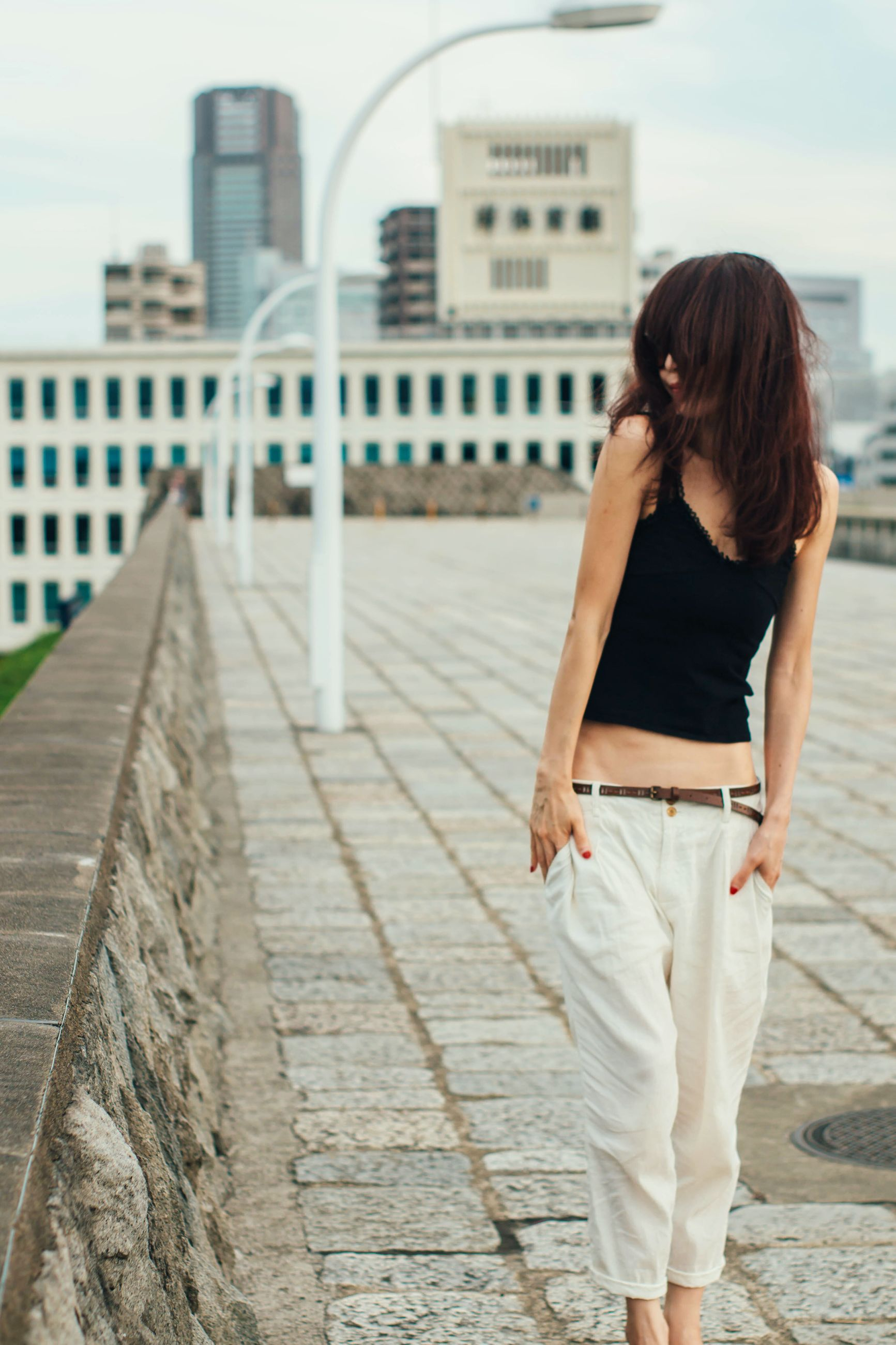 real people, casual clothing, full length, built structure, one person, building exterior, architecture, outdoors, young adult, leisure activity, lifestyles, rear view, day, young women, walking, standing, retaining wall, city, sky