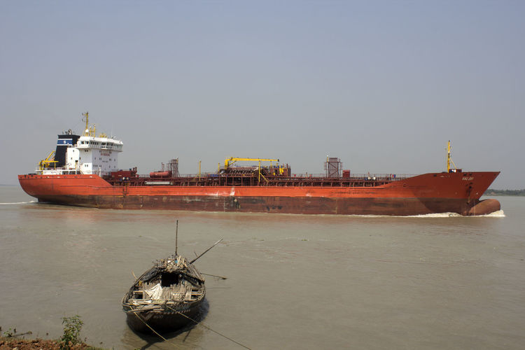 Ship moored in sea against clear sky
