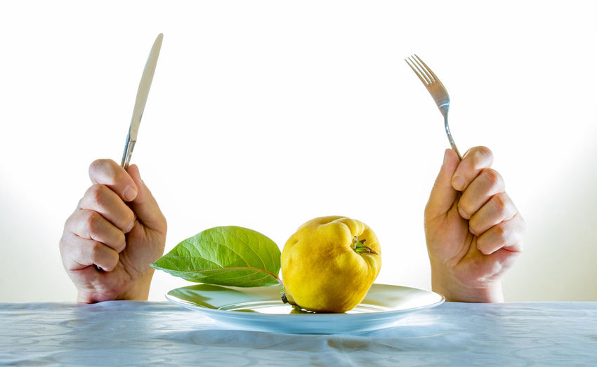 Close-up of hand holding fork and table knife with fruit in plate on table