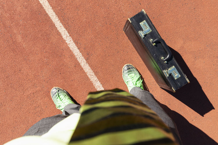 Low section of man standing by briefcase on running track