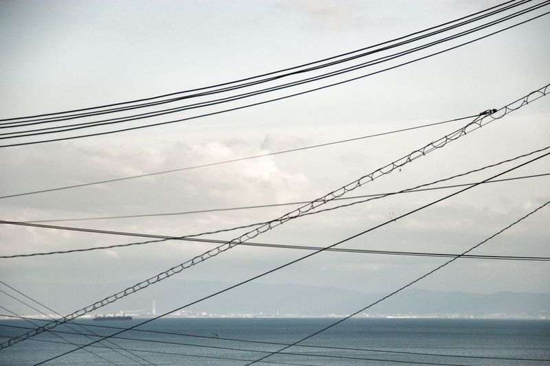 Low Angle View Of Tangled Cables Over Sea Against Cloudy Sky