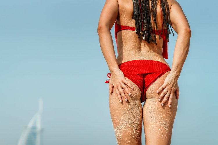 Midsection of woman wearing bikini while standing against sky