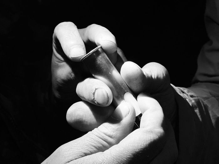 Close-up of hands holding electronic cigarette in darkroom