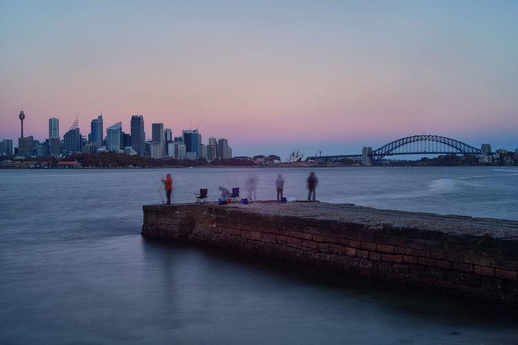 People Fishing On Pier Against Sydney Harbor Bridge