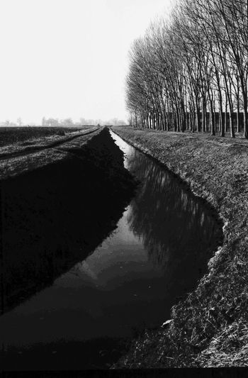 Canal amidst field against clear sky
