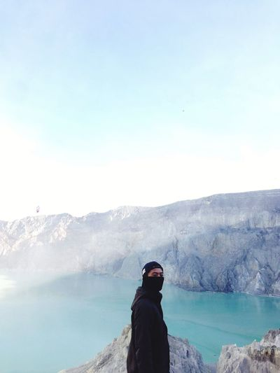 The man looking at the mountains in the sky above the ijen crater