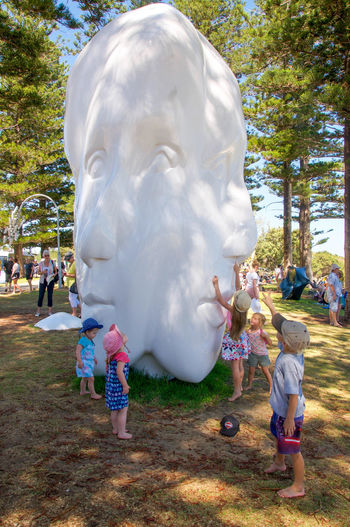 Kids touching a large multi-face sculpture at the interactive Sculptures by the Sea at Cottesloe Beach in Western Australia. Art Arts And Entertainment Beach Childhood Cottesloe Face Families Feeling Festival HEAD Interactive  Kids Modern Outdoors People Sculpture Sculptures By The Sea Smooth Statue Touching Tourism Tourist Attraction  Tourists Western Australia White