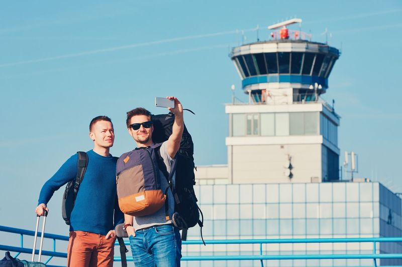 Man with friend taking selfie from mobile phone outside airport