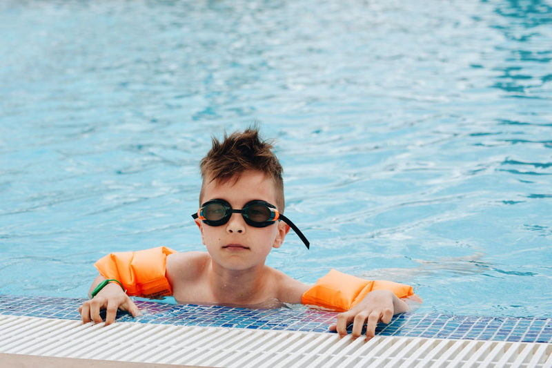 Portrait of boy wearing swimming goggles in pool