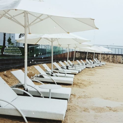 Empty white lounge chairs with umbrellas at beach