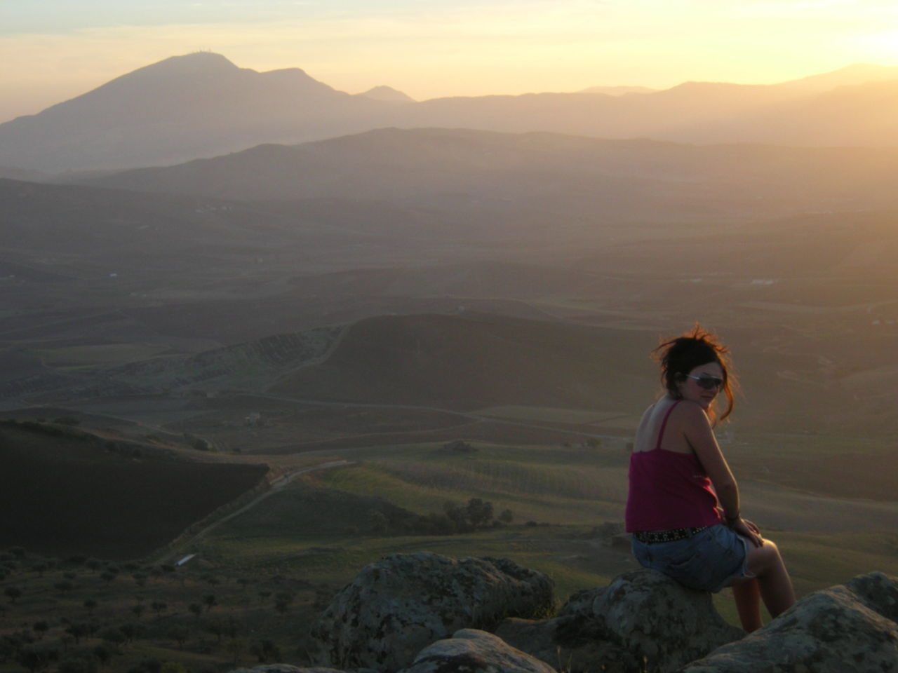 Side View Of Young Woman Sitting On Rock During Sunset