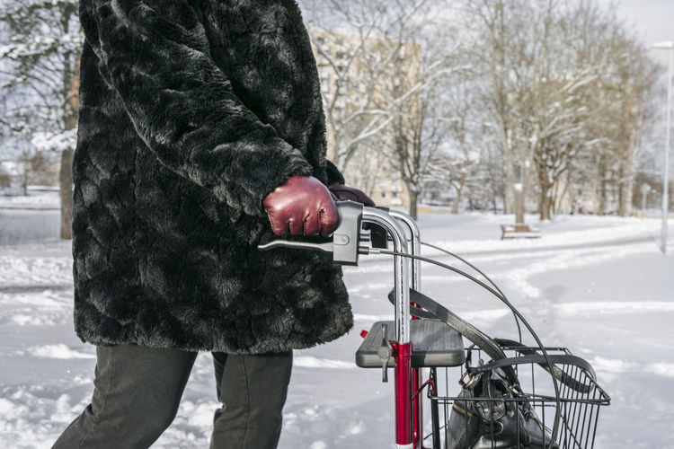 Man with bicycle on snow in city