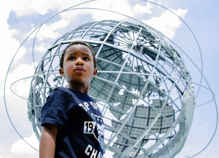 Low angle view of boy standing against unisphere