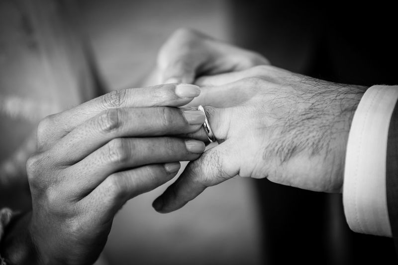 Close-up of woman putting ring on man