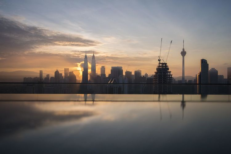 Petronas towers amidst buildings against sky during sunrise in city