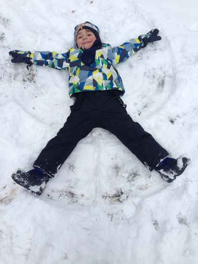 High Angle Portrait Of Cute Boy Making Snow Angel During Winter