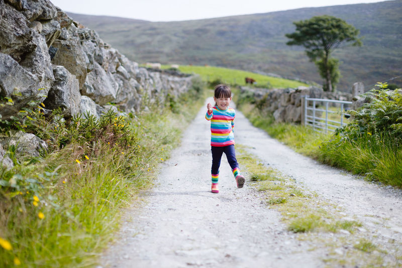 Young girl walking on summer countryside road