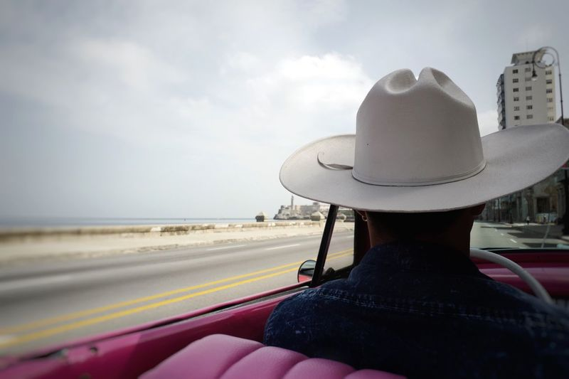 Rear View Of Man Riding Convertible Car By Sea Against Sky
