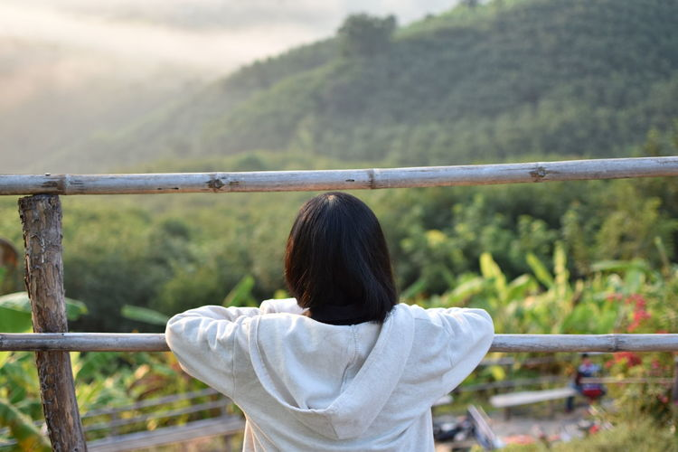 Rear View Of Woman Looking At Mountains Through Railing