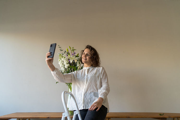 Young woman photographing with mobile phone on table