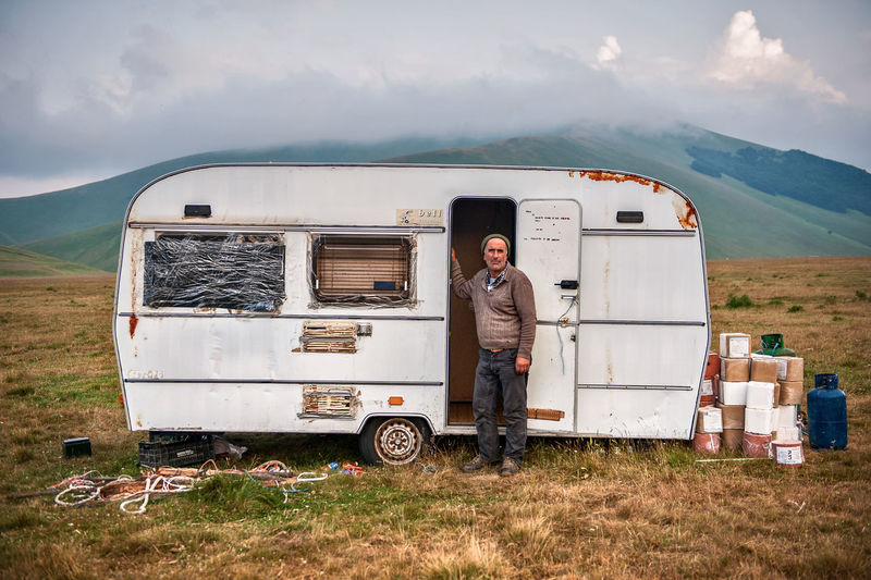 Man Standing With Travel Trailer On Mountain Against Sky