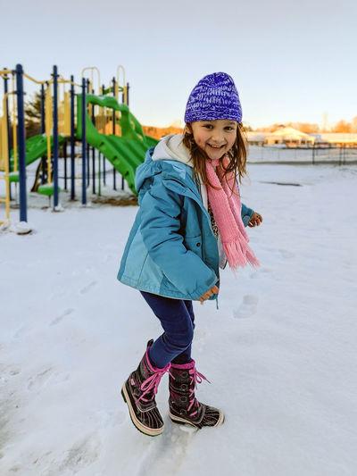 Full length of girl standing on snow covered land