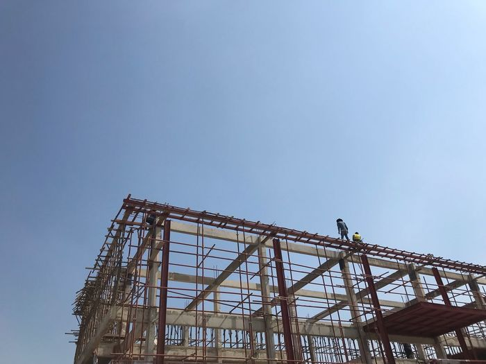 Low angle view of people working at construction site against clear blue sky