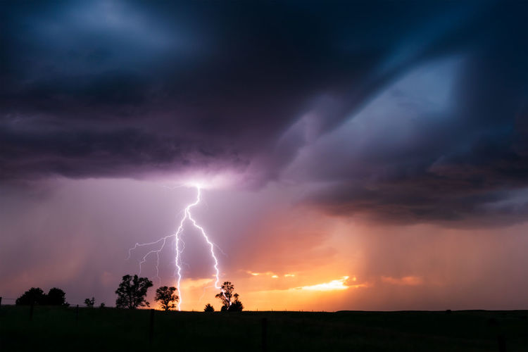 Low angle view of lightning against dramatic sky during sunset