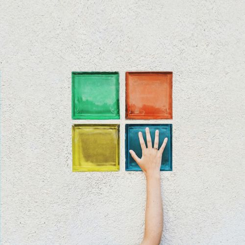 Close-up of hand against multi colored wall