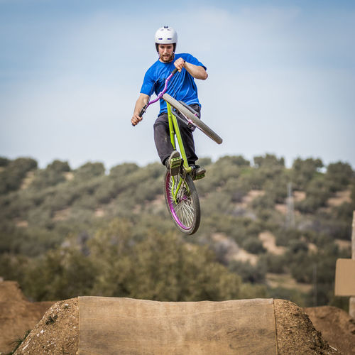 Sportsman performing trick and flying on a bike in nature on dirtjump circuit Extreme Bike Biker Casual Clothing Day Dirtjump Extreme Sports Full Length Helmet Jumping Leisure Activity Lifestyles Men Mid-air Motion Nature One Person Outdoors Real People Riding RISK Skill  Sport Stunt Transportation