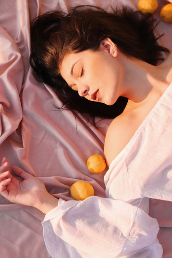 Midsection of woman lying on bed