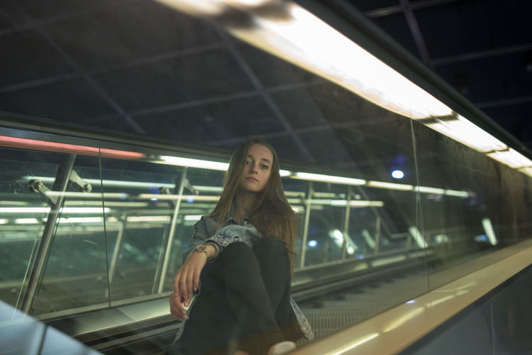 Portrait of young woman sitting on escalator seen through glass